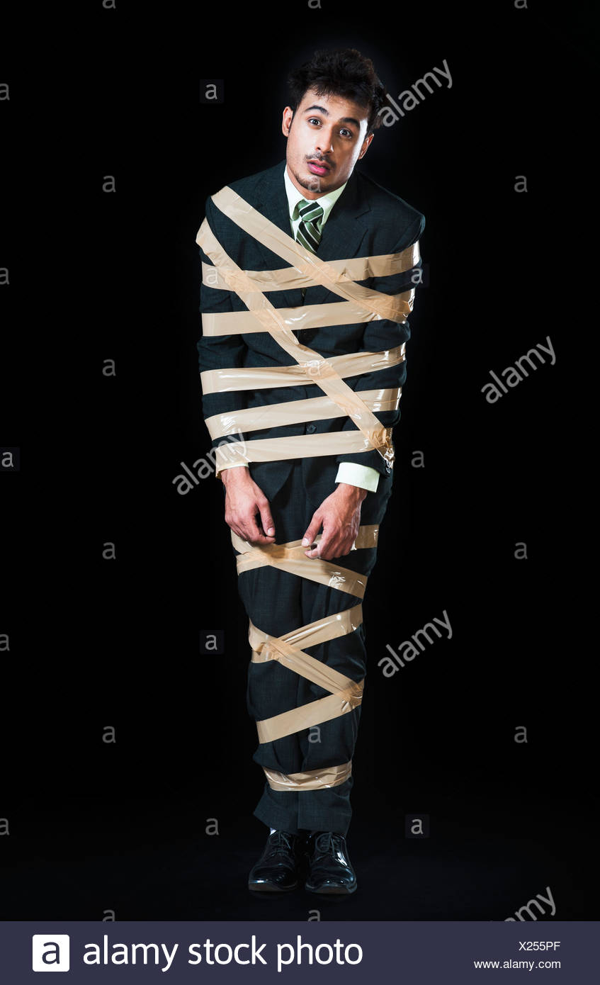 Businessman tied up with adhesive tape and looking sad - Stock Image
