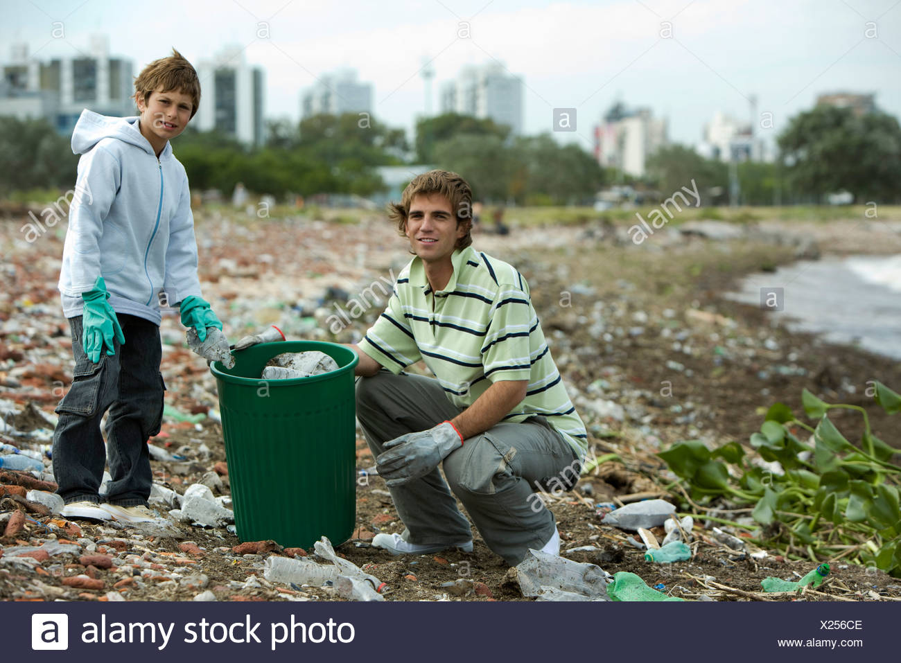 Young male and boy picking up trash on polluted shore - Stock Image