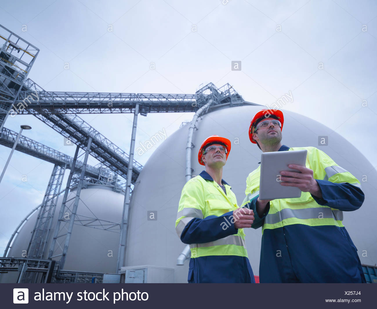 Workers using digital tablet at biomass facility, low angle view - Stock Image