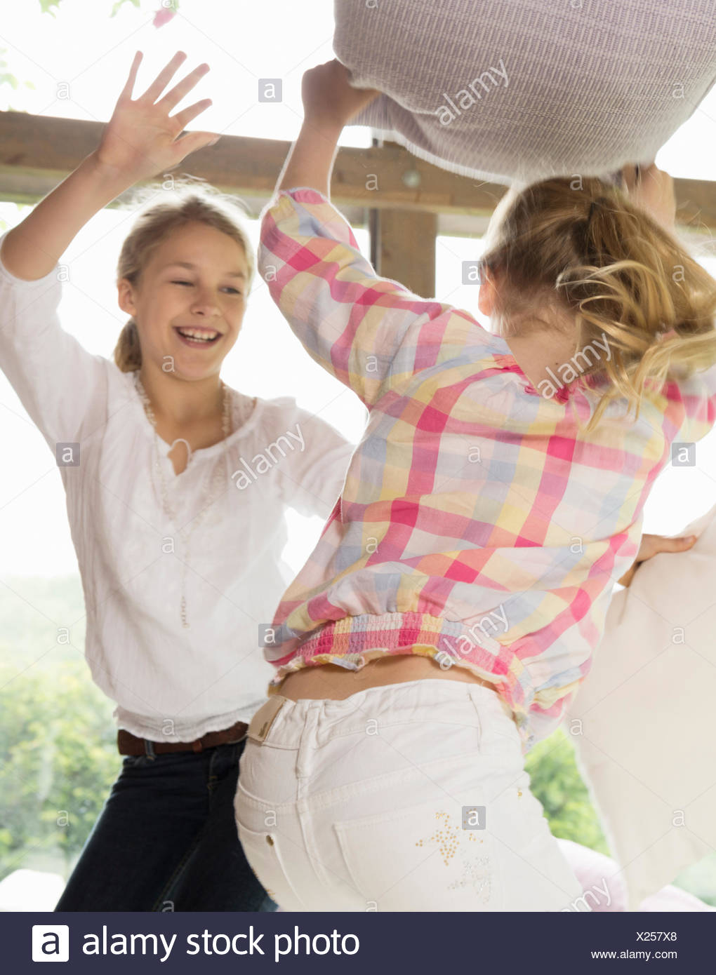 Two sisters having pillow fight - Stock Image