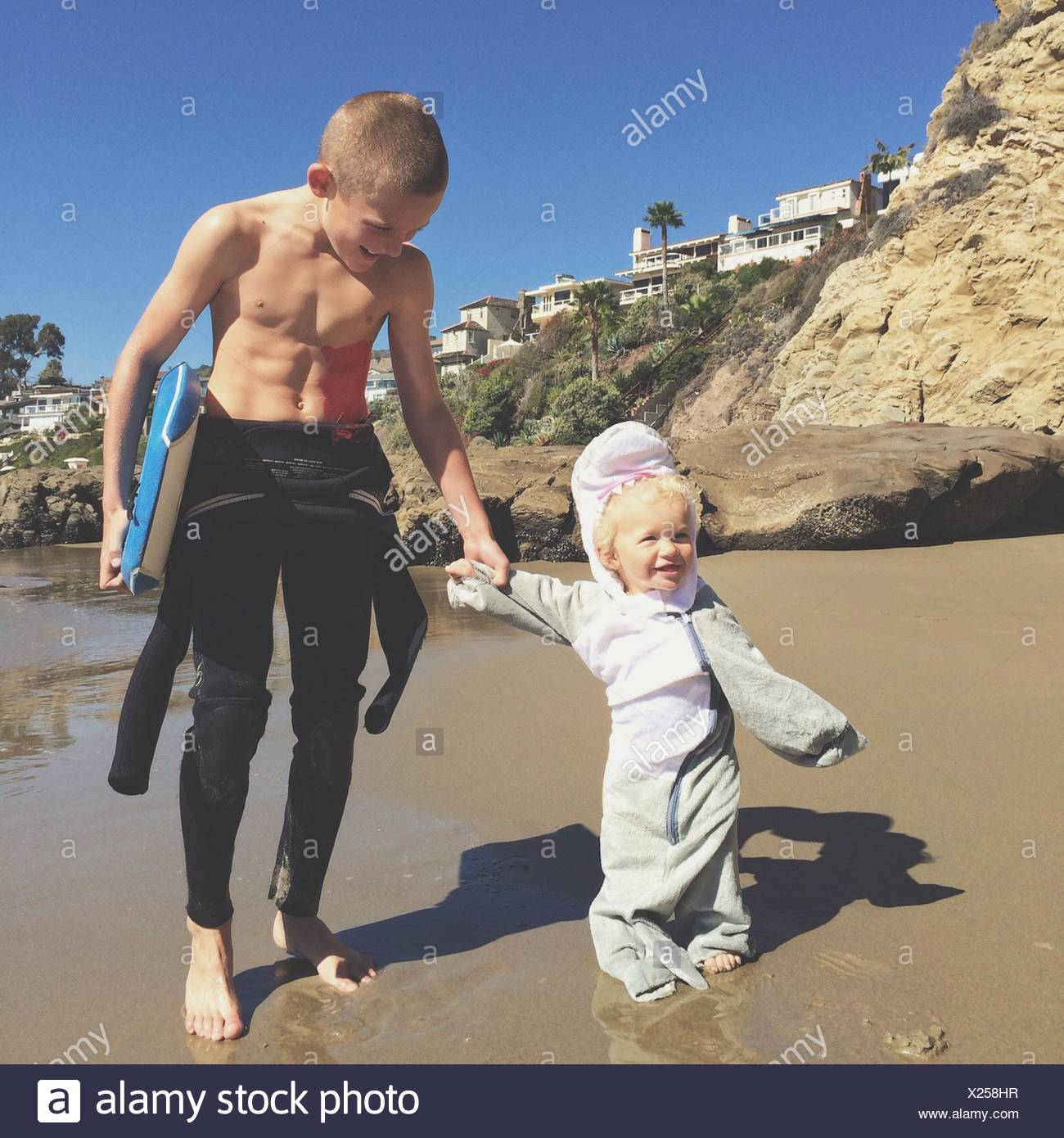 Two brothers holding hands on the beach with a surfboard - Stock Image