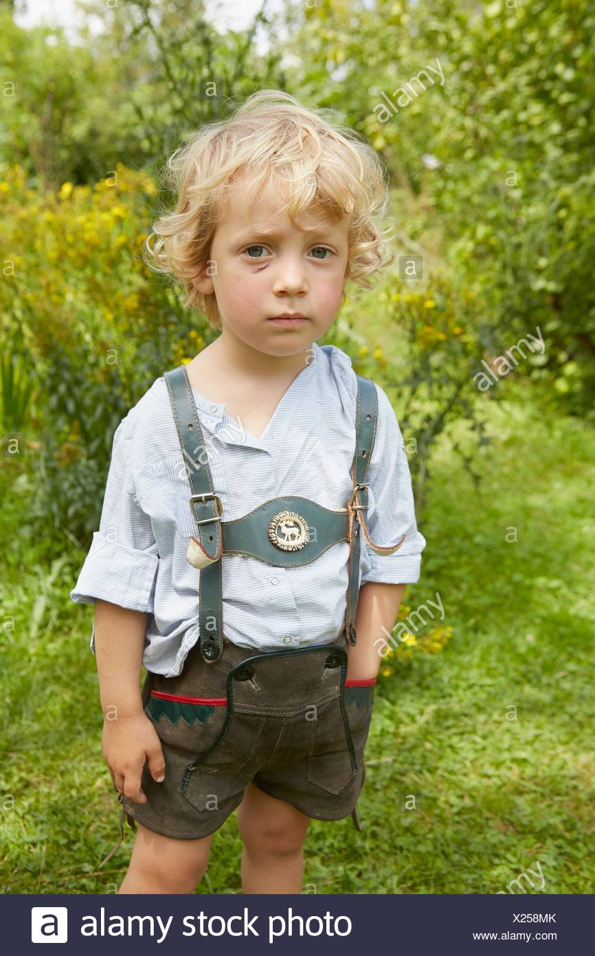 Portrait of sad boy with scratched face wearing lederhosen - Stock Image