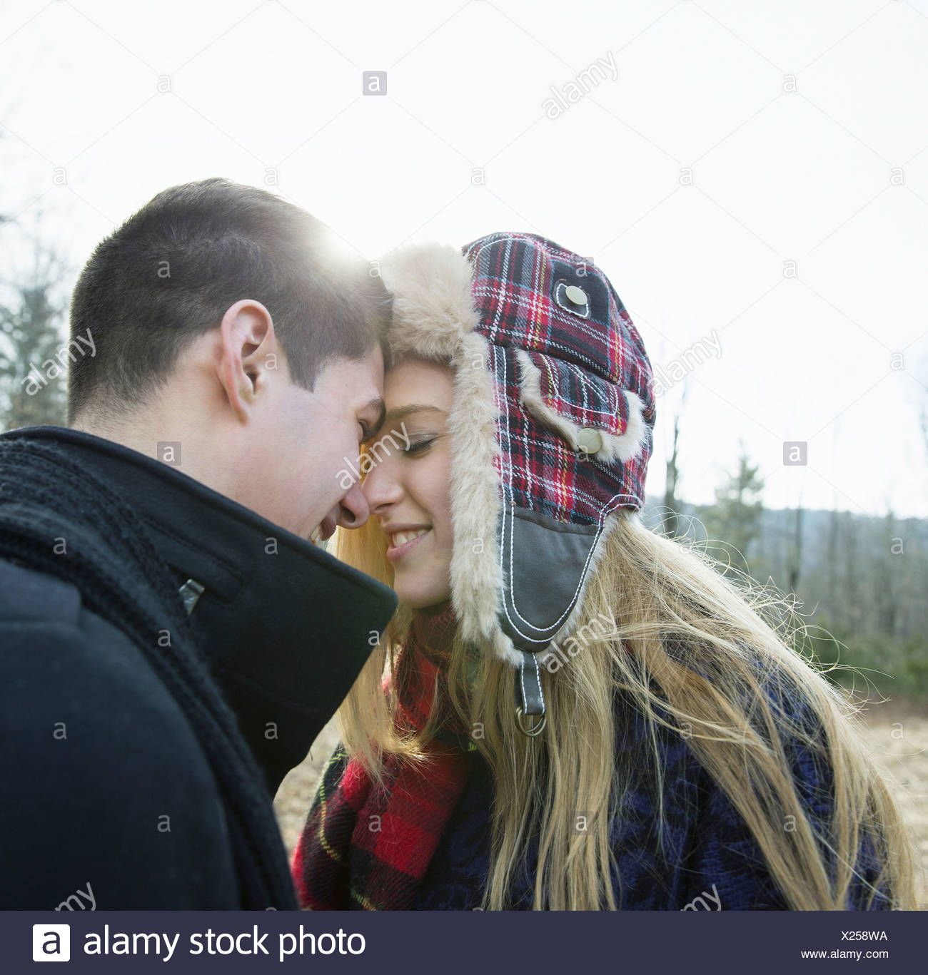 A couple young man and woman face to face embracing outdoors on a cold winter day - Stock Image