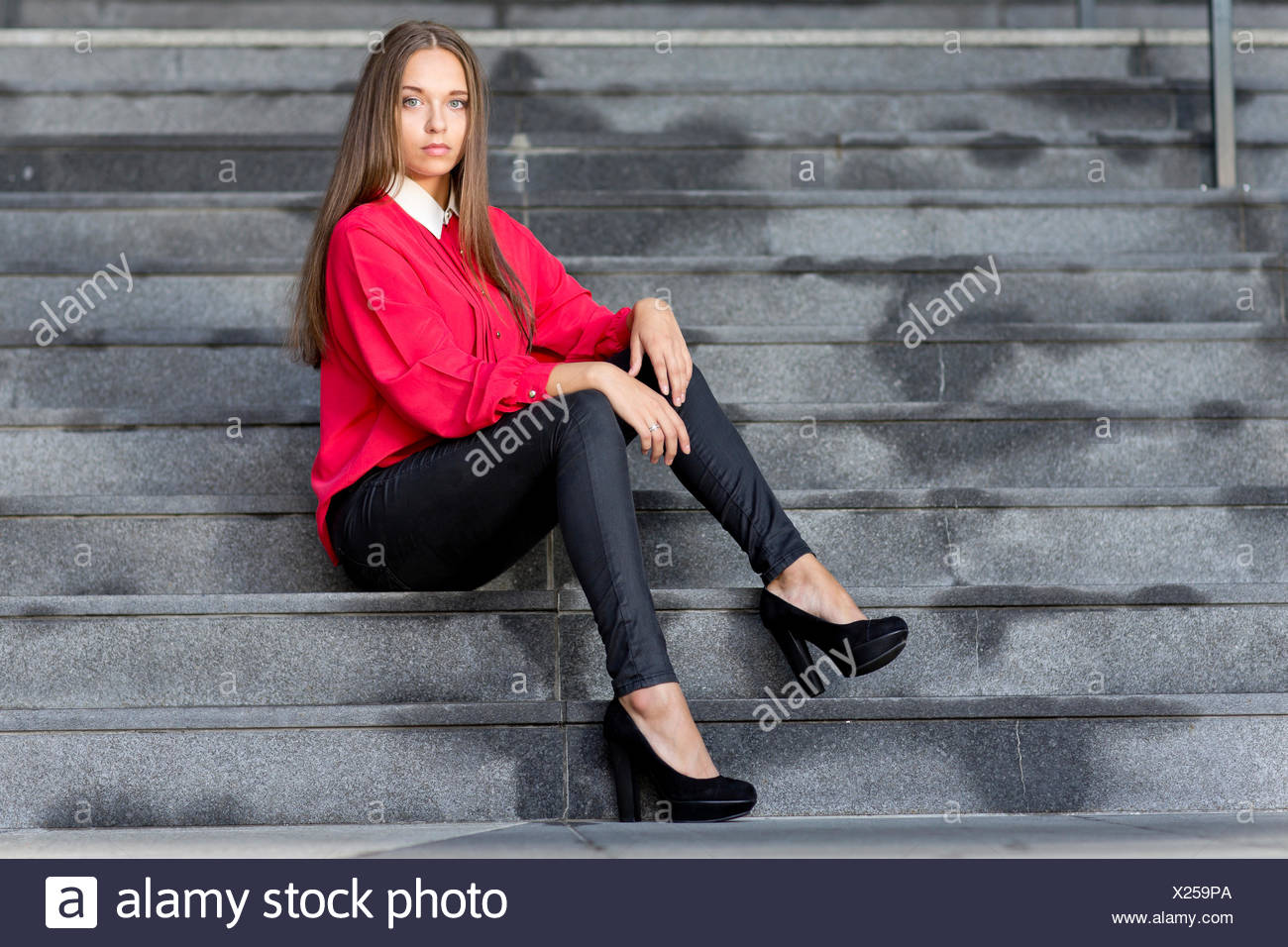 2f7365d43 Young woman wearing a red top, black jeans and high heels posing while  sitting on
