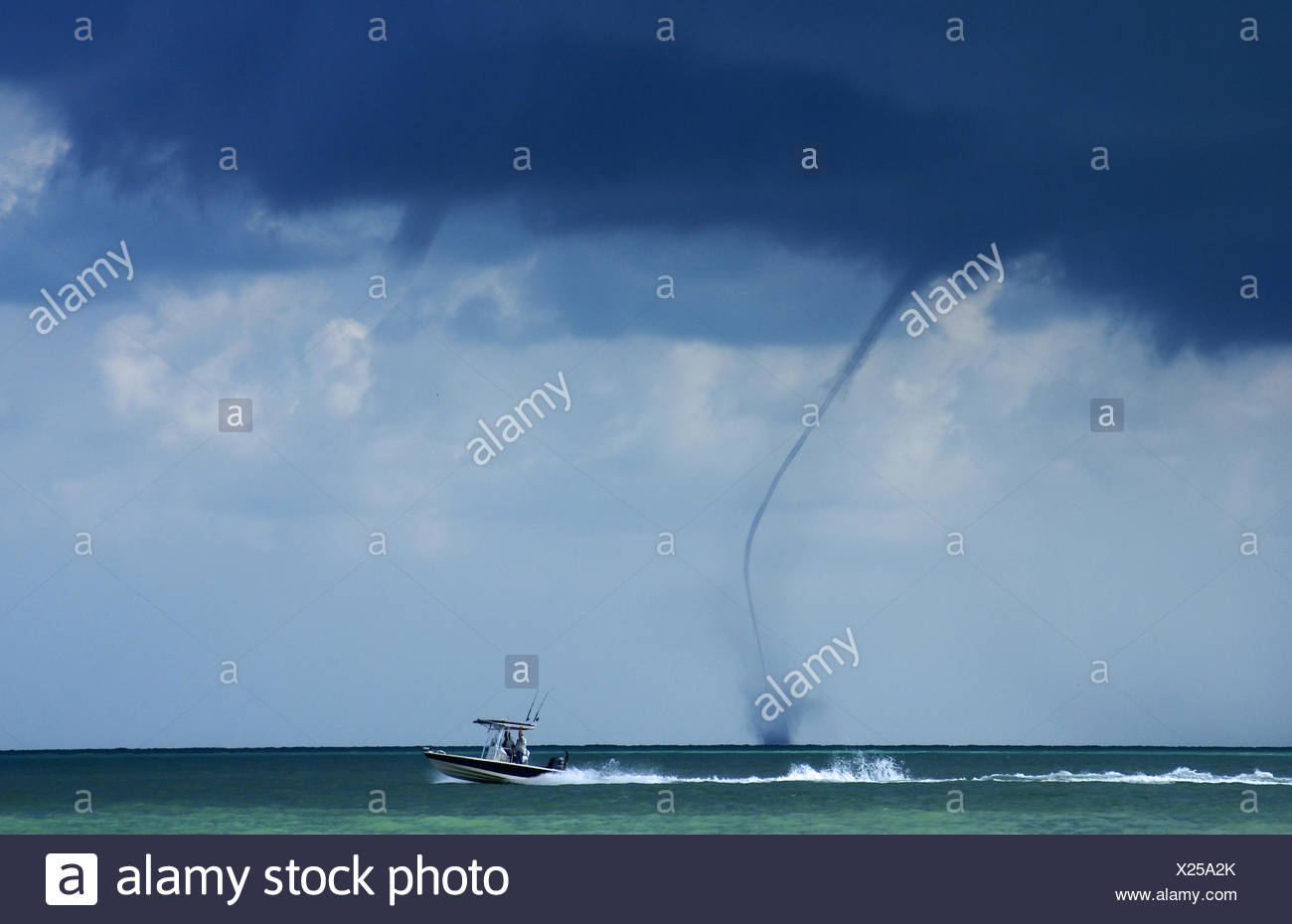 Water spout and motor boat on sea - Stock Image