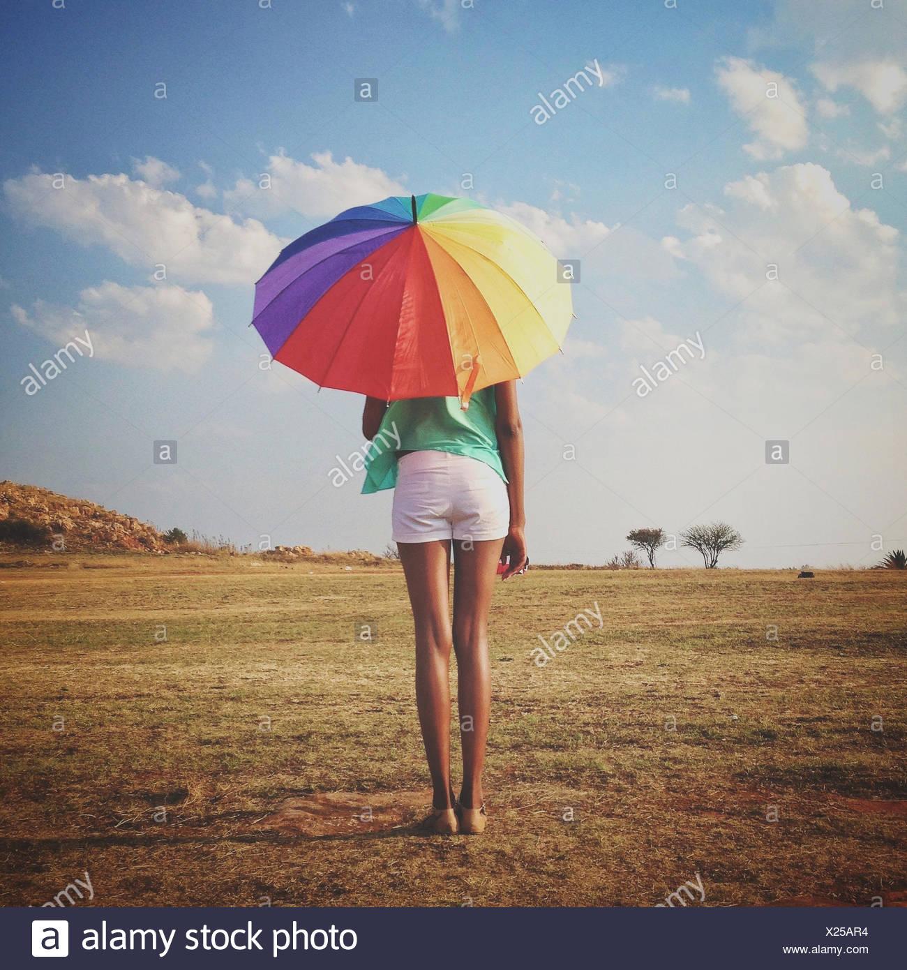 Woman holding a multi coloured Umbrella, Roodepoort, Johannesburg, Gauteng, South Africa Stock Photo