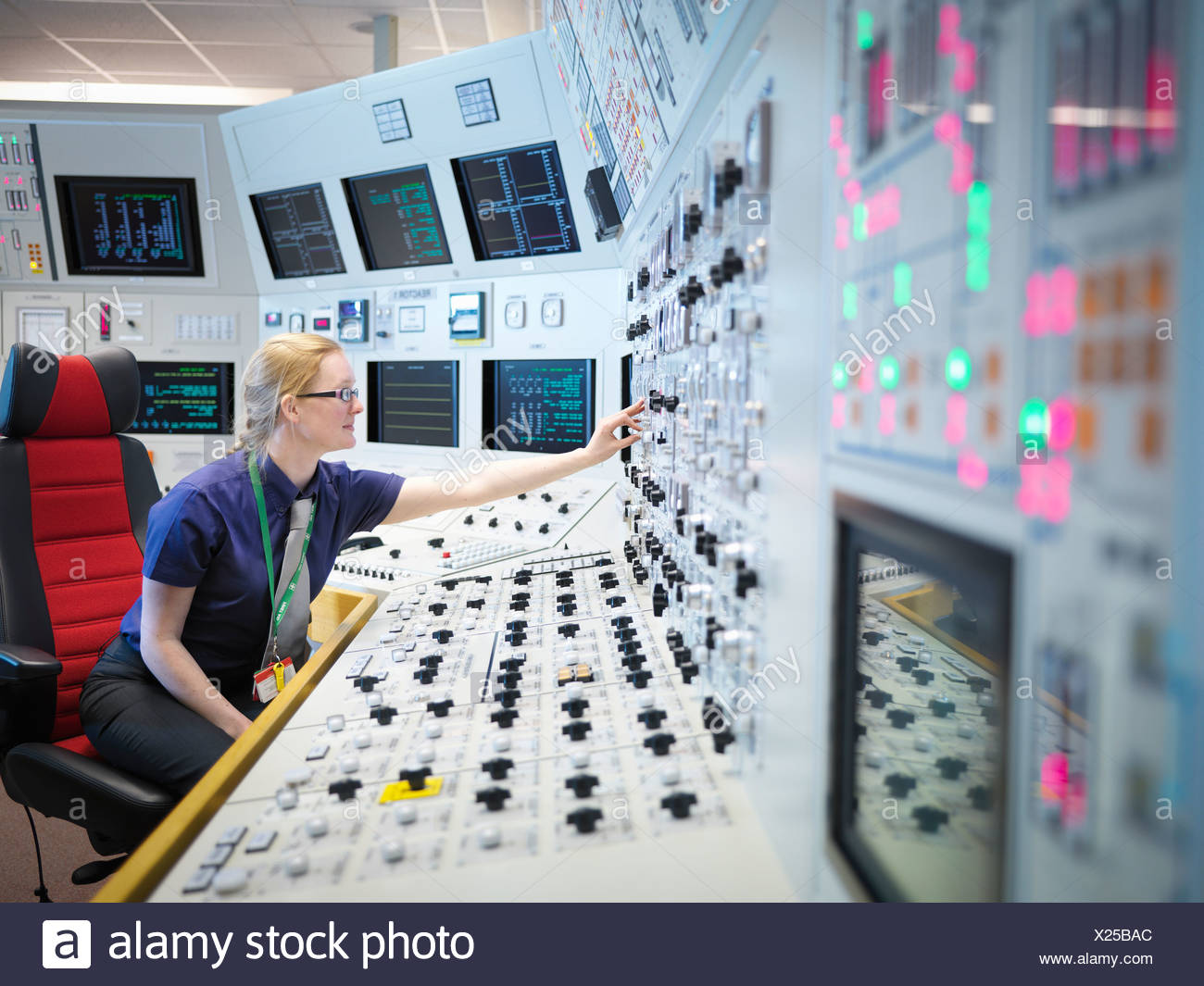 Female operator in nuclear power station control room simulator - Stock Image