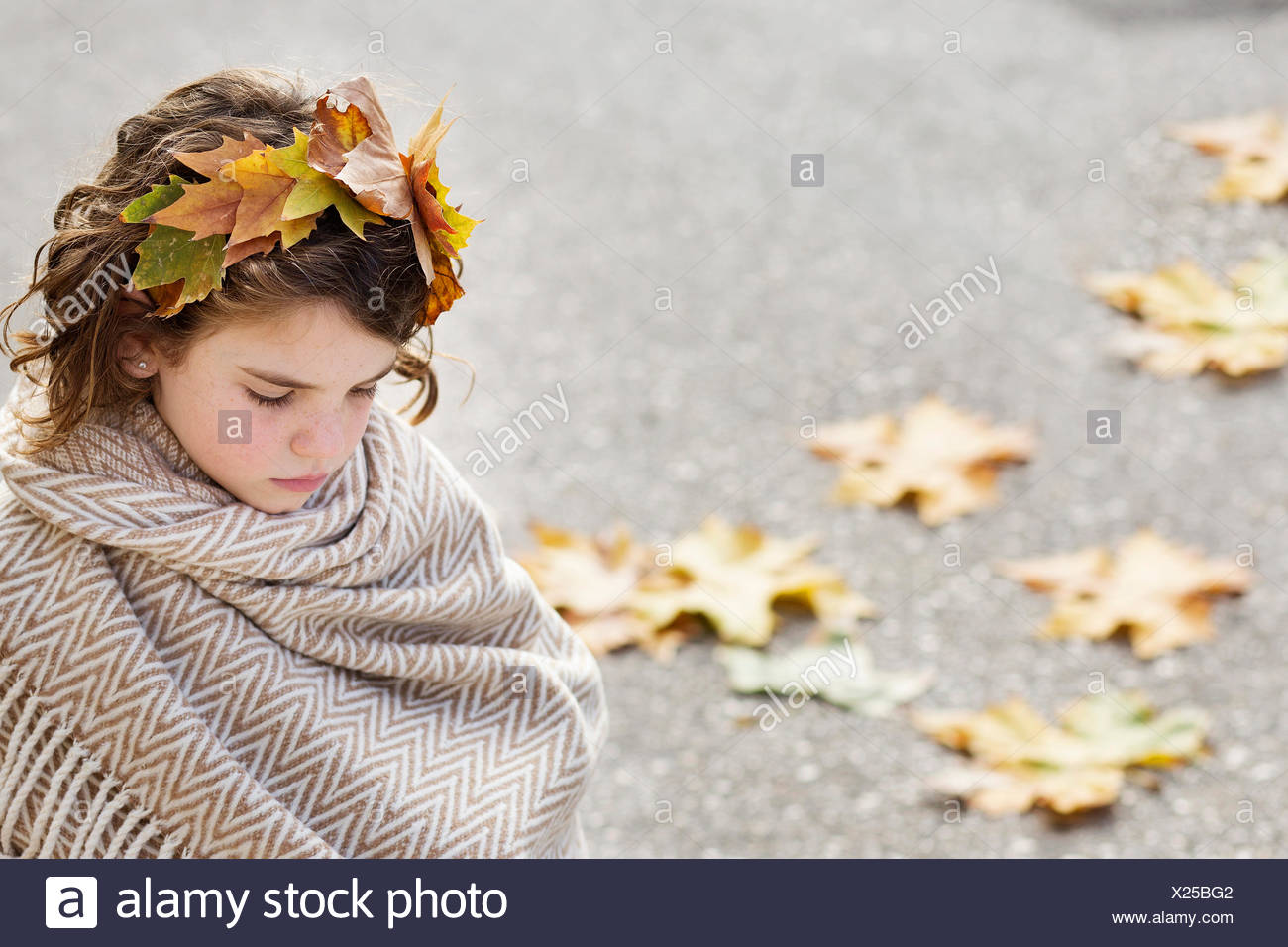 Girl wrapped in a blanket wearing headdress made of autumn leaves - Stock Image