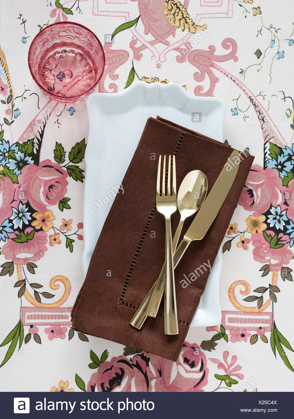 Plate with napkin and cutlery on floral tablecloth - Stock Image