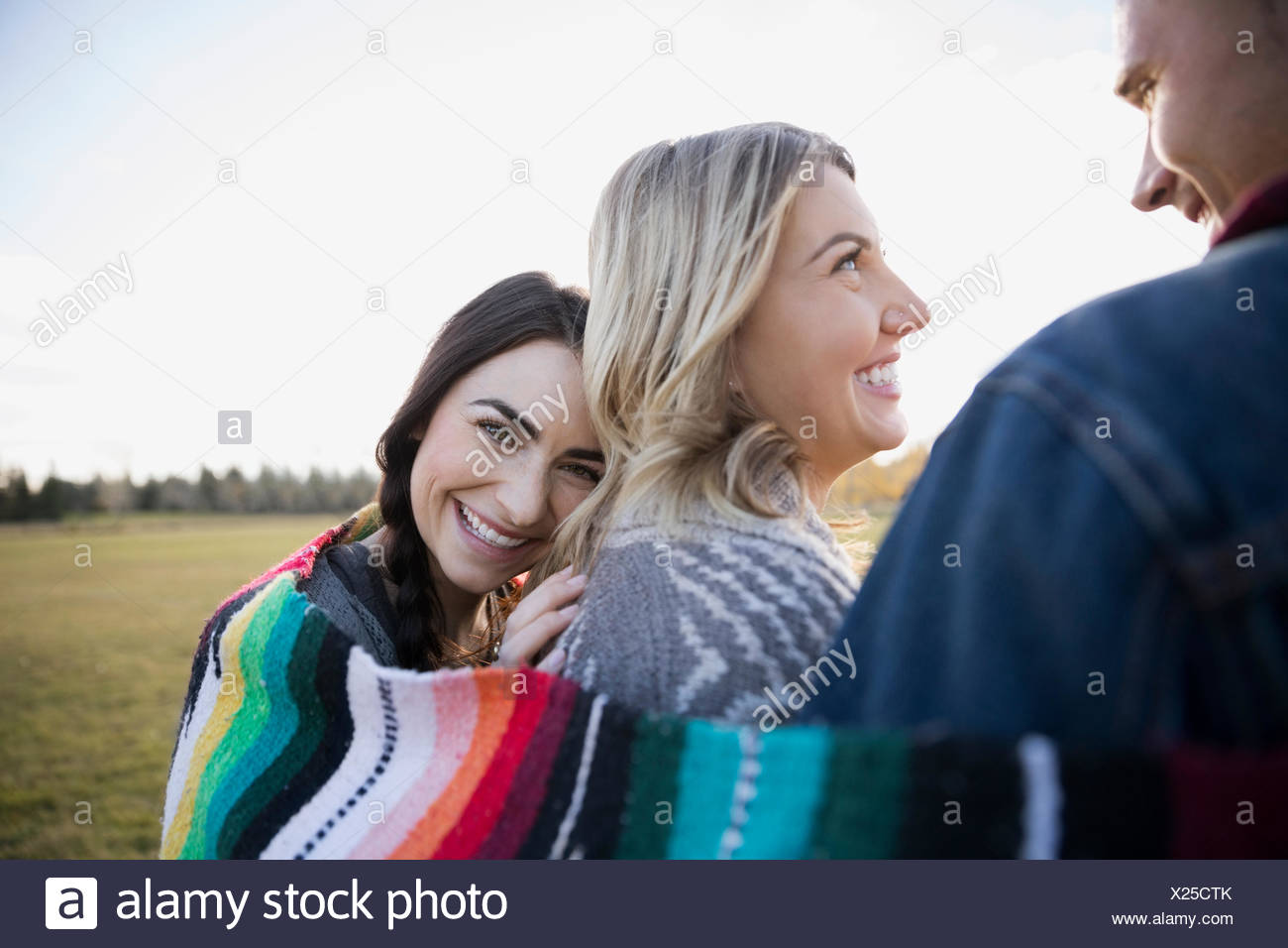 Portrait smiling woman wrapped in a blanket with friends - Stock Image