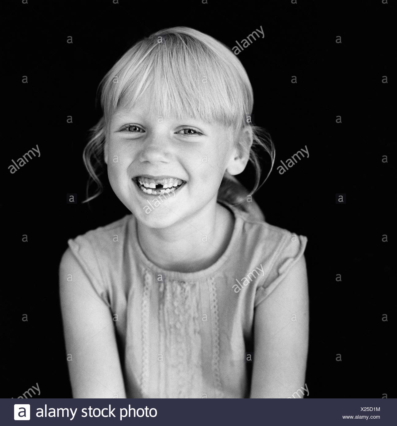 black and white blonde children only girls happy indoors one person only optimism portrait positive smiling tooth toothless - Stock Image
