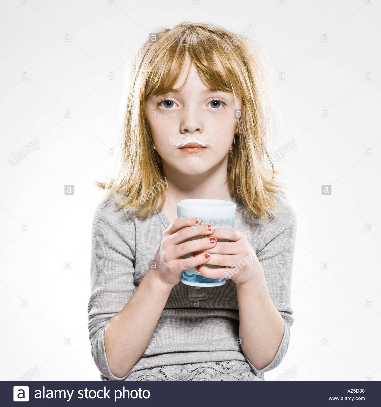 girl looking at the camera with milk mustache - Stock Image