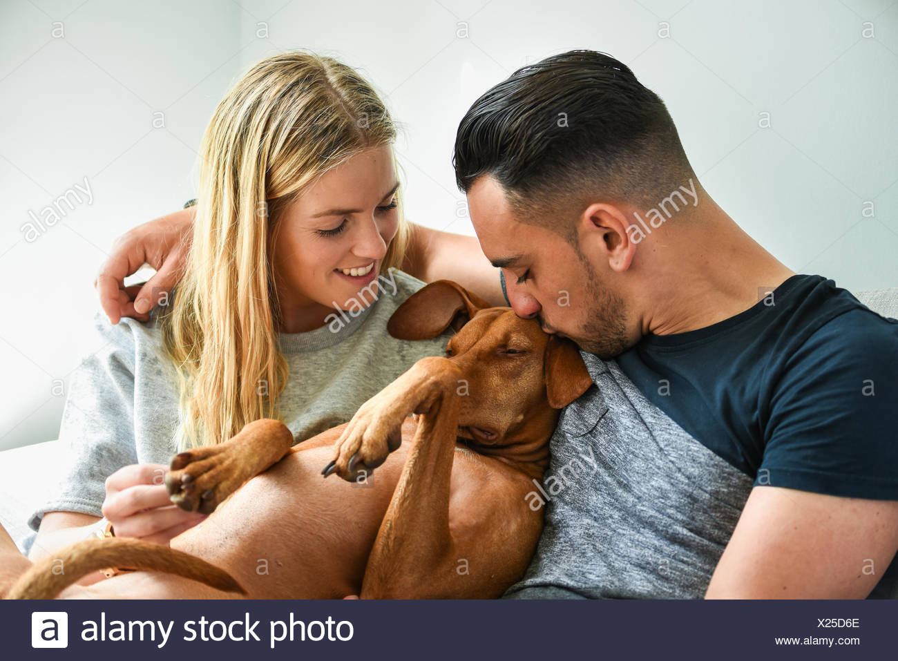Close-up of man kissing dog with girlfriend - Stock Image