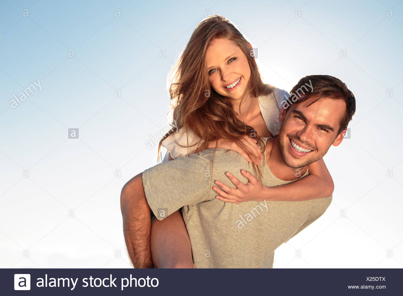 Man giving a piggy back to his girlfriend - Stock Image