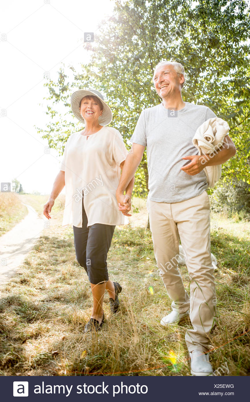 Happy senior couple walking with blanket in nature - Stock Image