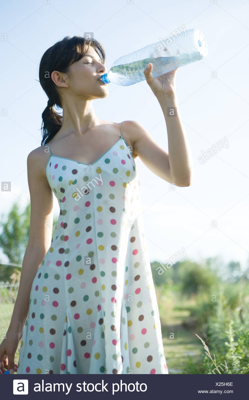 Young woman drinking from bottle of water, eyes closed - Stock Image