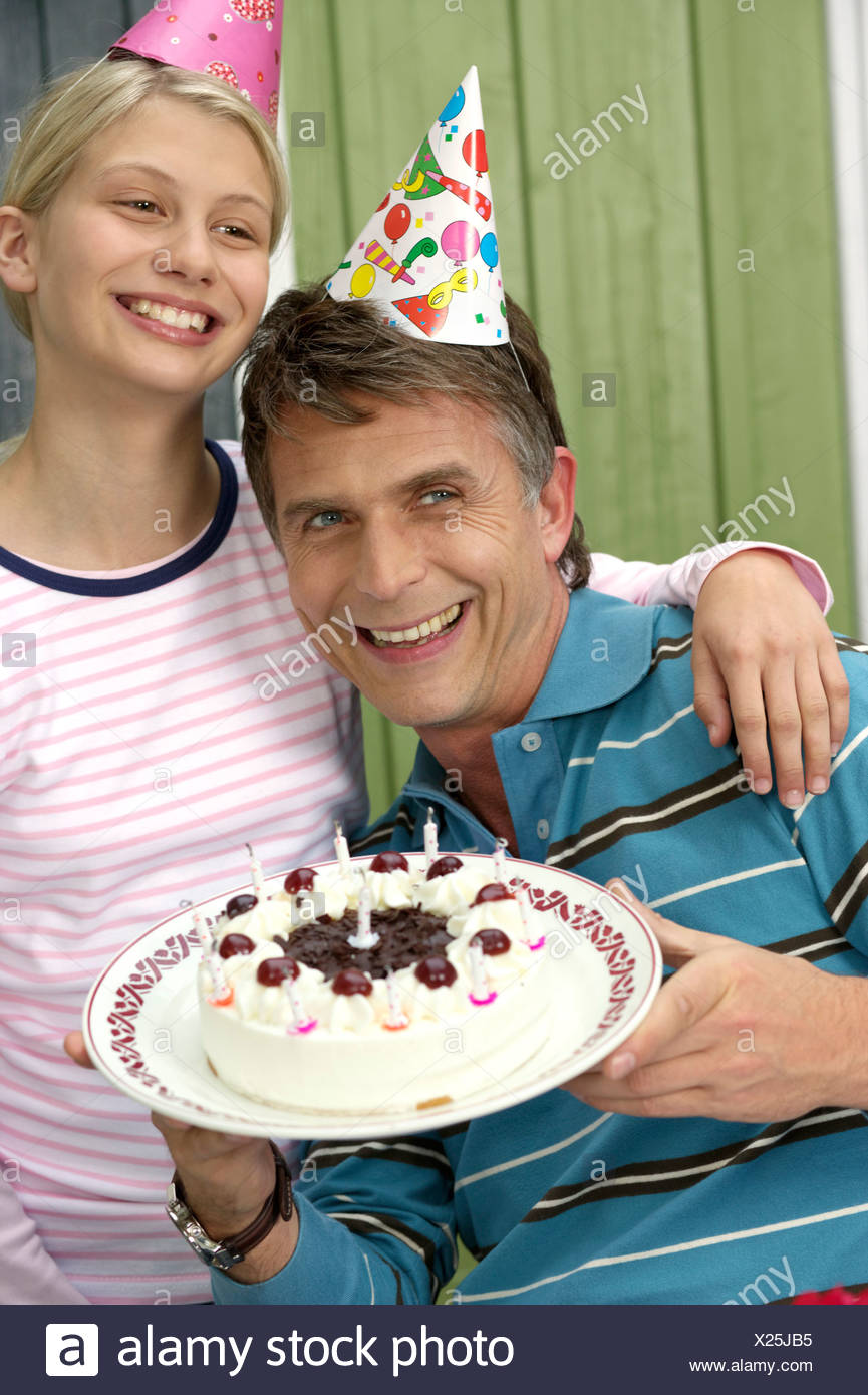 Mature Man With A Birthday Cake In His Hand Next To His Blond