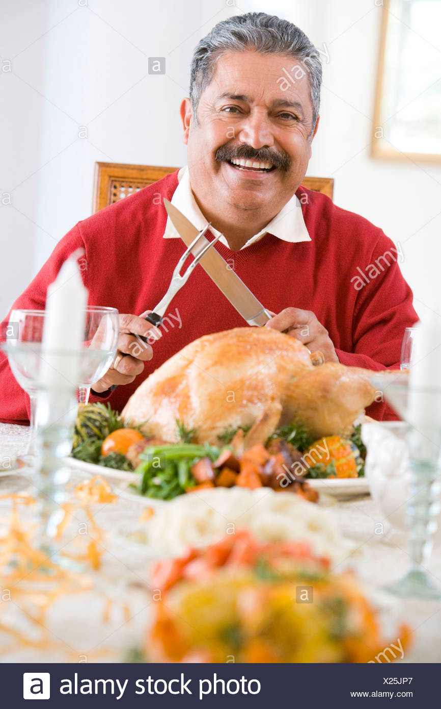 Senior Man Excitedly Getting Ready To Carve The Turkey - Stock Image
