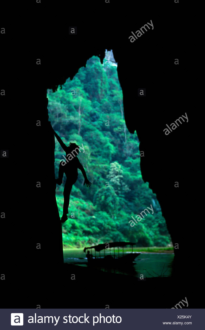 Man rock climbing over river with boat in background. Song Nang River, Vietnam - Stock Image