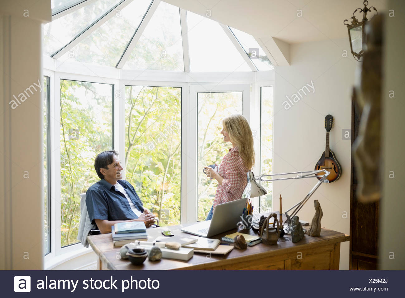 Couple talking in home office - Stock Image