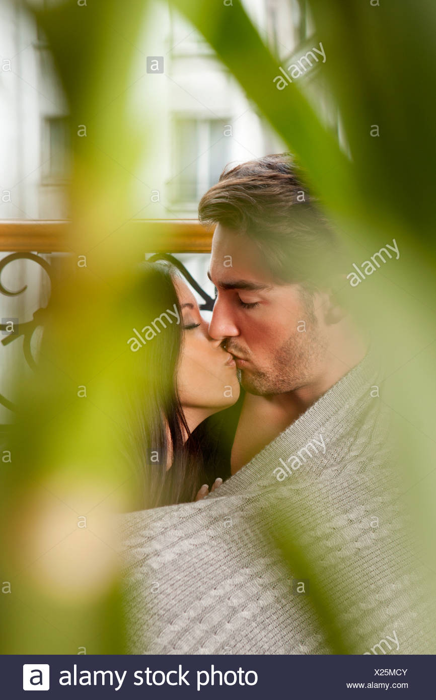 Kissing couple wrapped in blanket - Stock Image