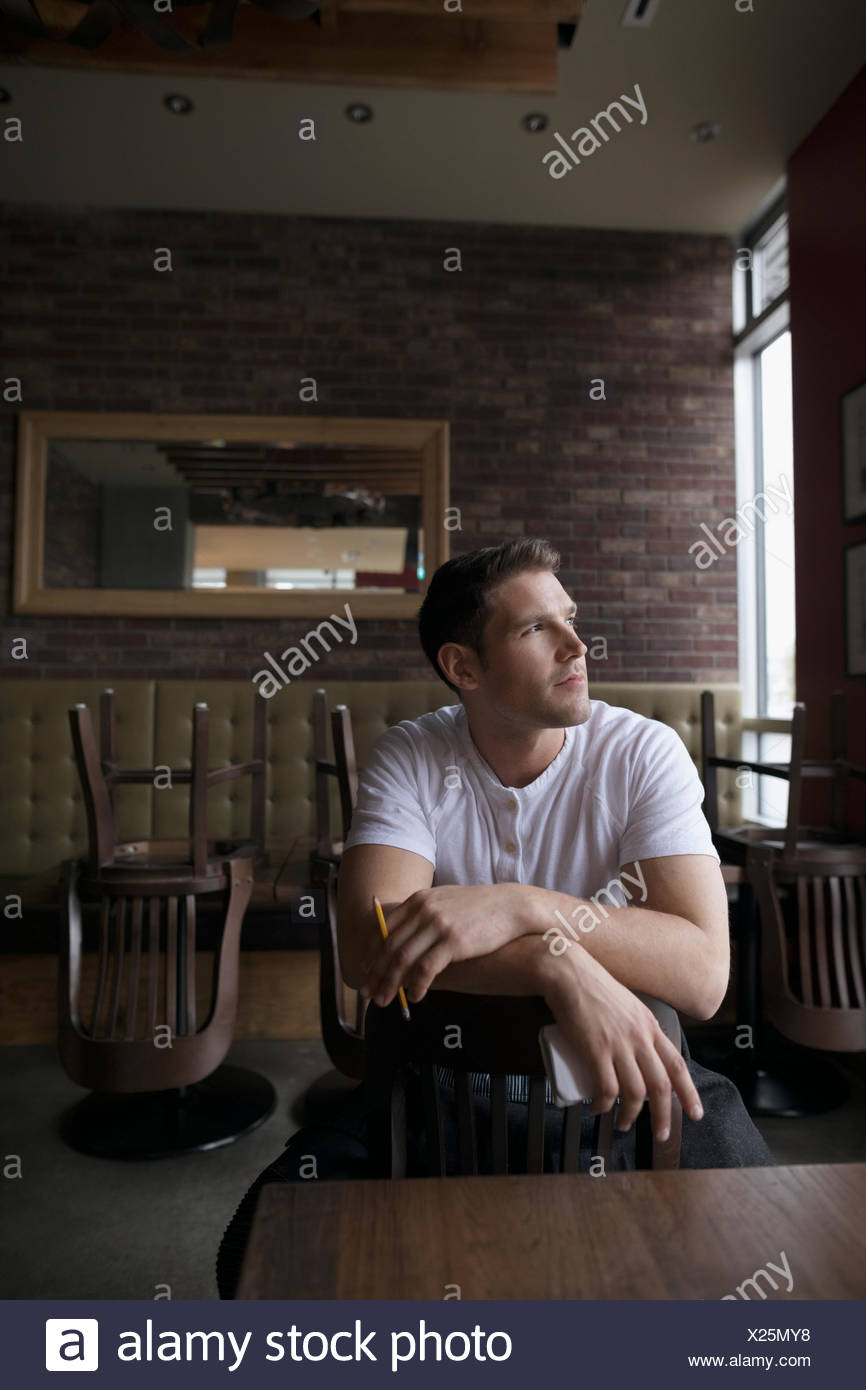 Pensive waiter straddling chair in diner, looking away - Stock Image