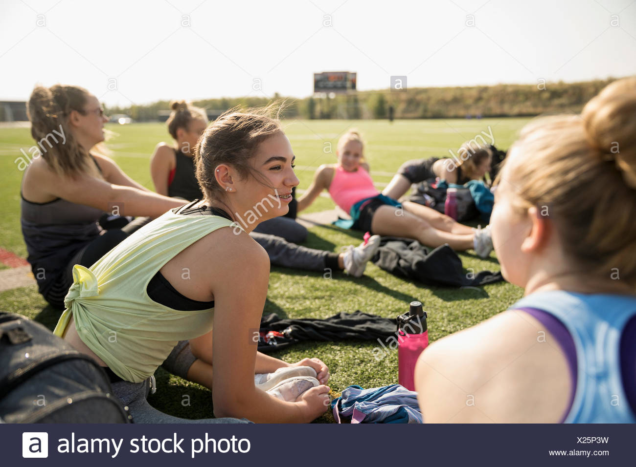 Teenage girl high school cheerleading team stretching and talking on sunny football field - Stock Image