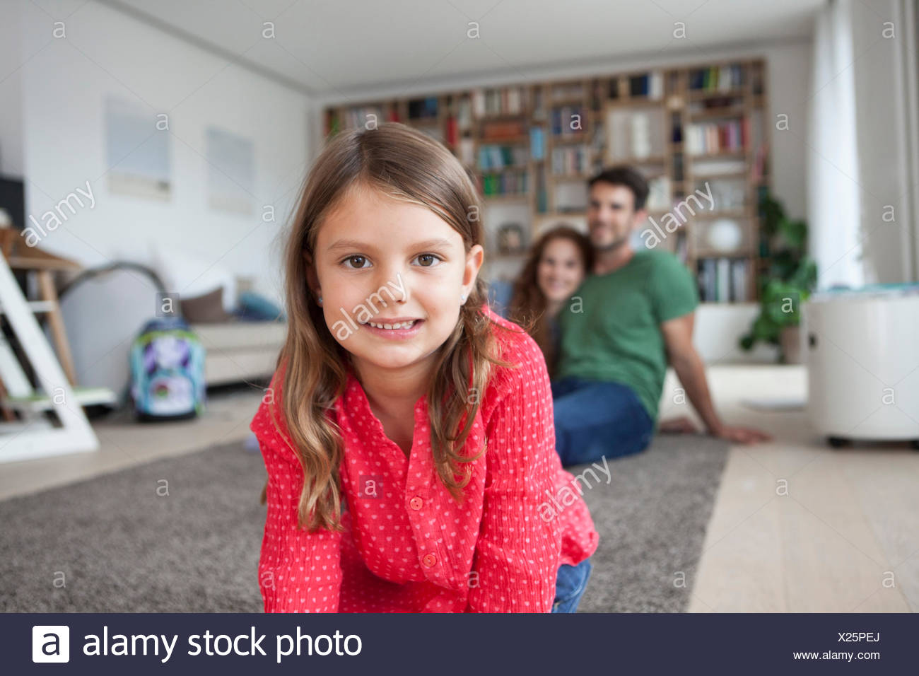Portrait of smiling little girl and her parents in the background in the  living room - Stock Image