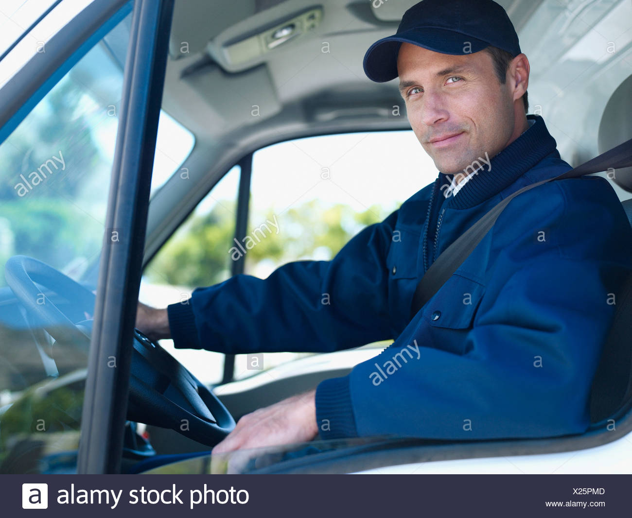 Delivery person driving van - Stock Image