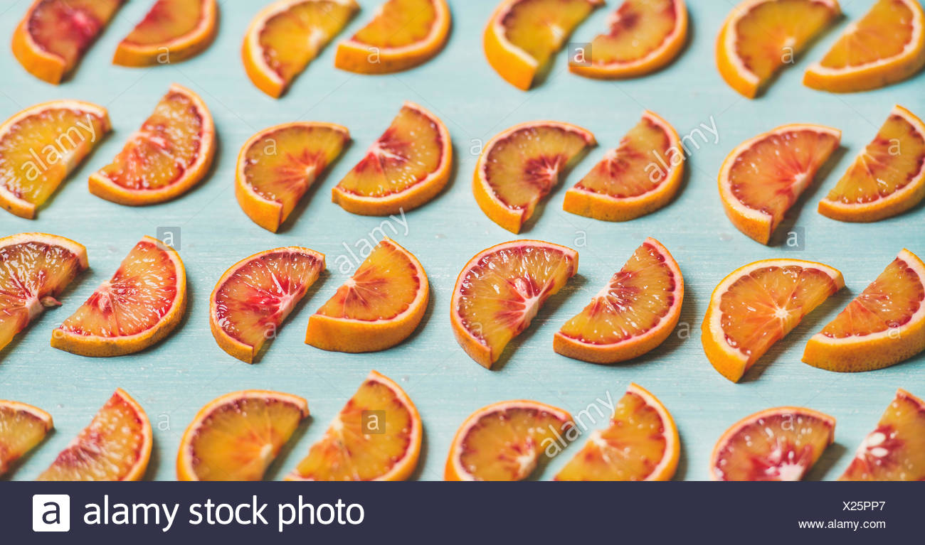 Natural fruit pattern concept. Fresh juicy blood orange slices placed in rows over light blue painted table background, selective focus - Stock Image
