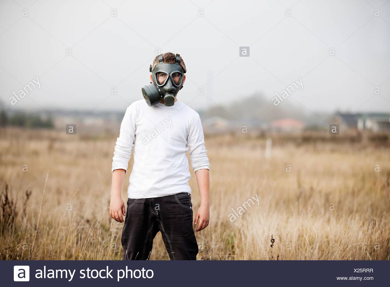 Boy wearing gas mask in wheatfield Stock Photo