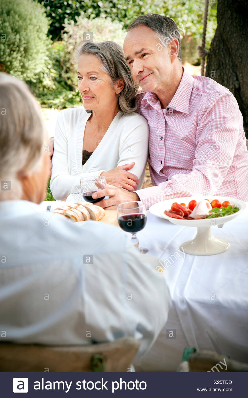 Portrait of mature couple sitting side by side at laid table in the garden - Stock Image