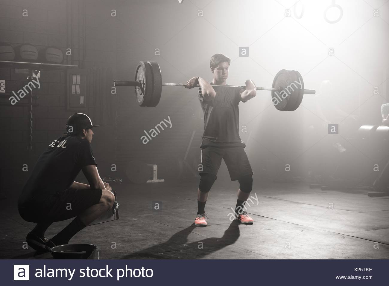 Young man lifting barbell while trainer looks on - Stock Image