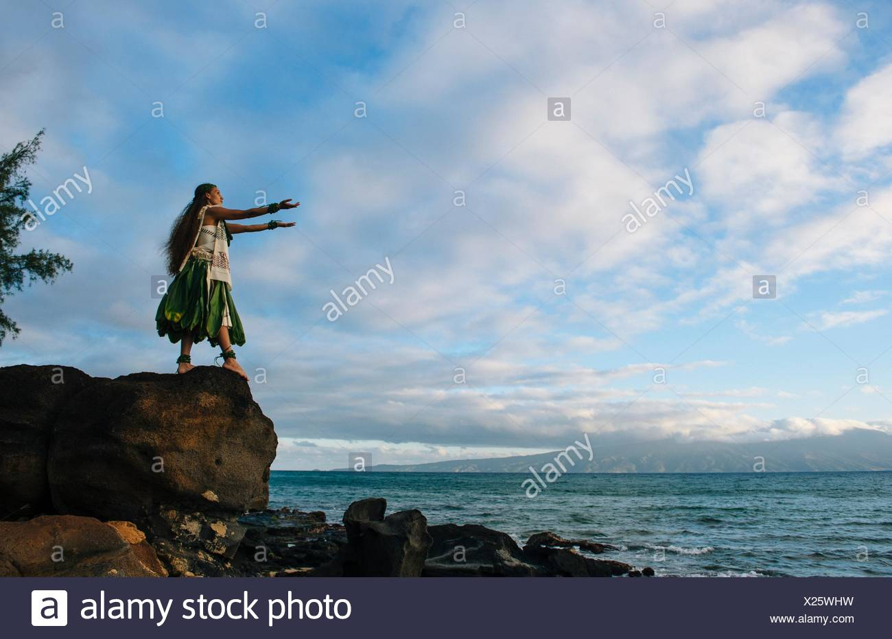 Woman hula dancing on top of coastal rocks wearing traditional costume, Maui, Hawaii, USA - Stock Image