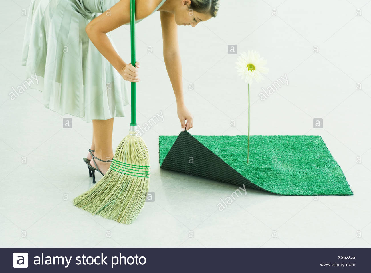 Woman bending over, broom in hand, lifting corner of artificial turf next to gerbera daisy - Stock Image