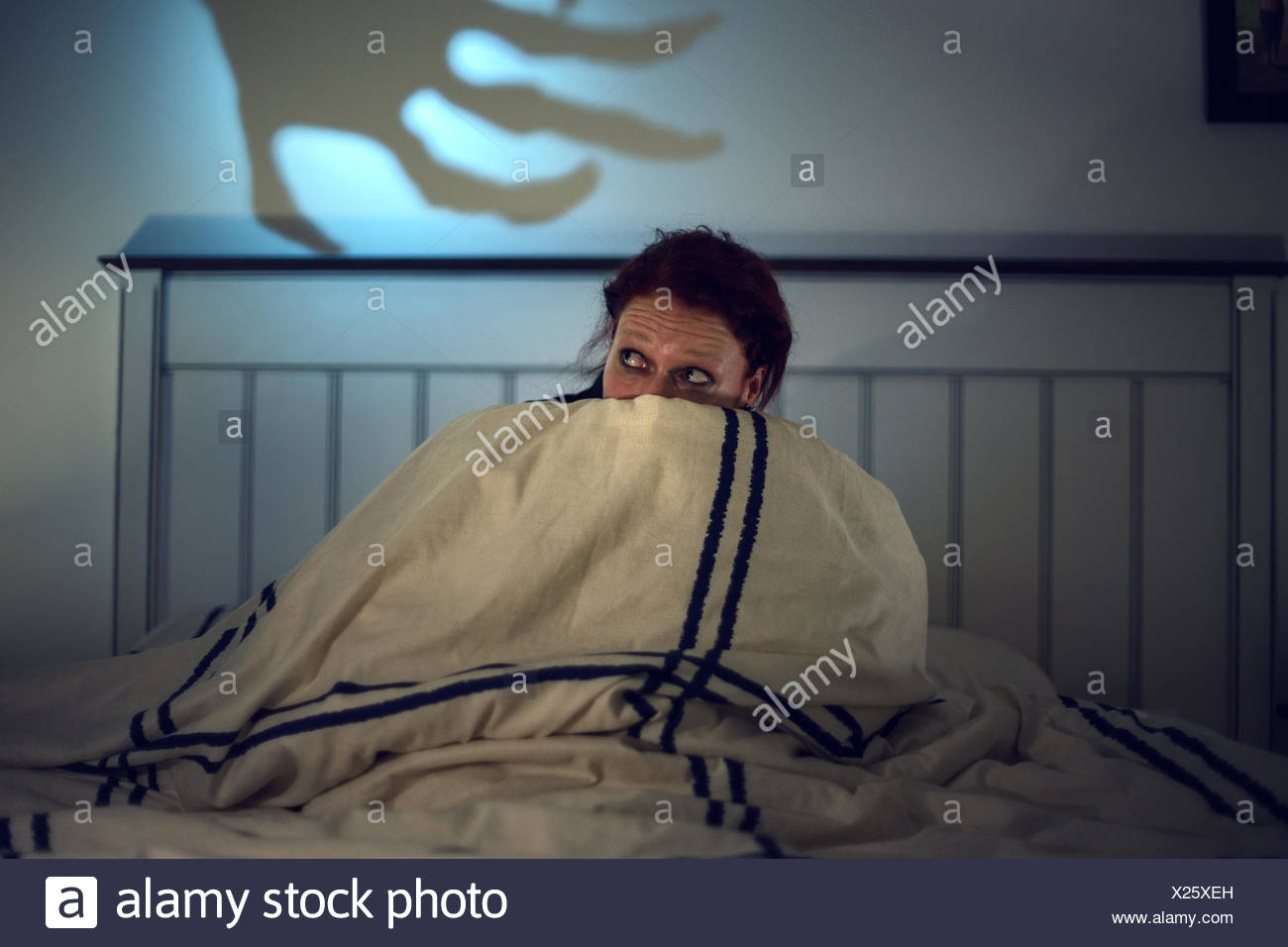 Frightened woman in bed, creepy shadow of a skeleton hand at back - Stock Image