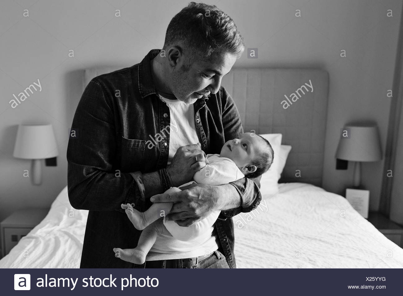 A man cradling a baby boy in his arms. - Stock Image