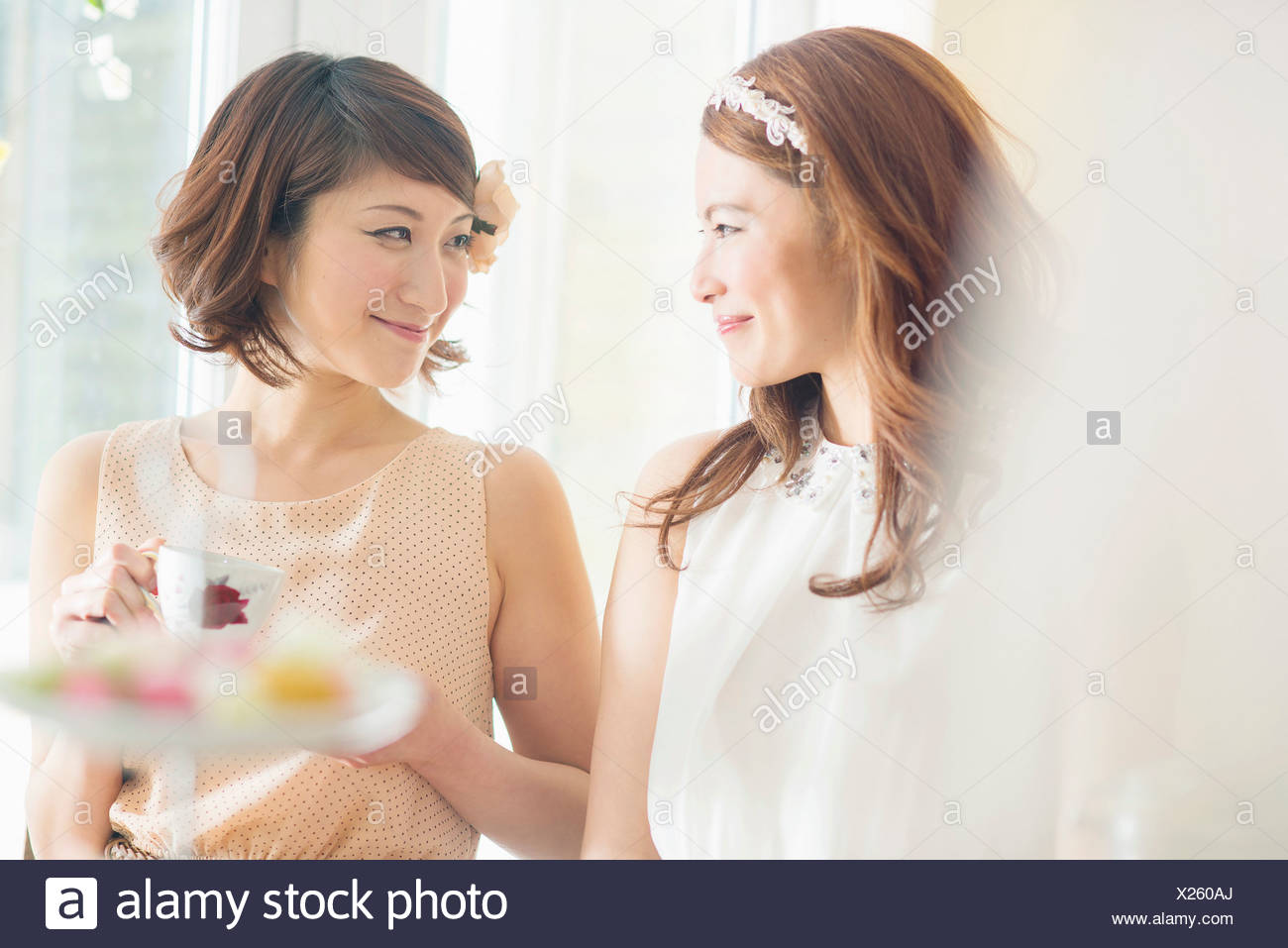 Two smiling women looking at each other - Stock Image