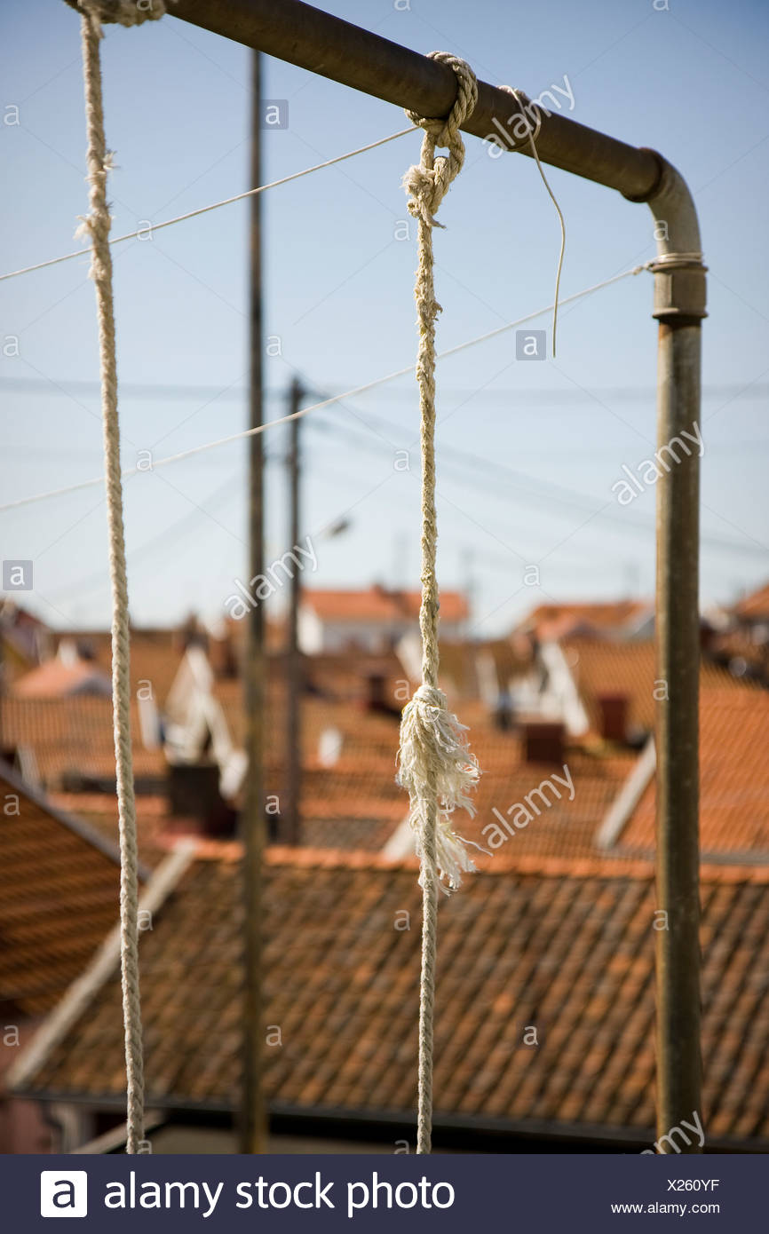 Close-up of swing ropes against rooftops - Stock Image
