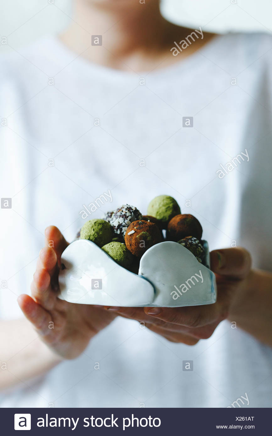 A woman holding a bowl of mixed matcha and chocolate homemade sweets - Stock Image