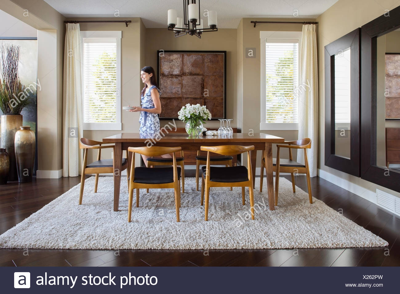 . Woman setting table in dining room Stock Photo  276729121   Alamy