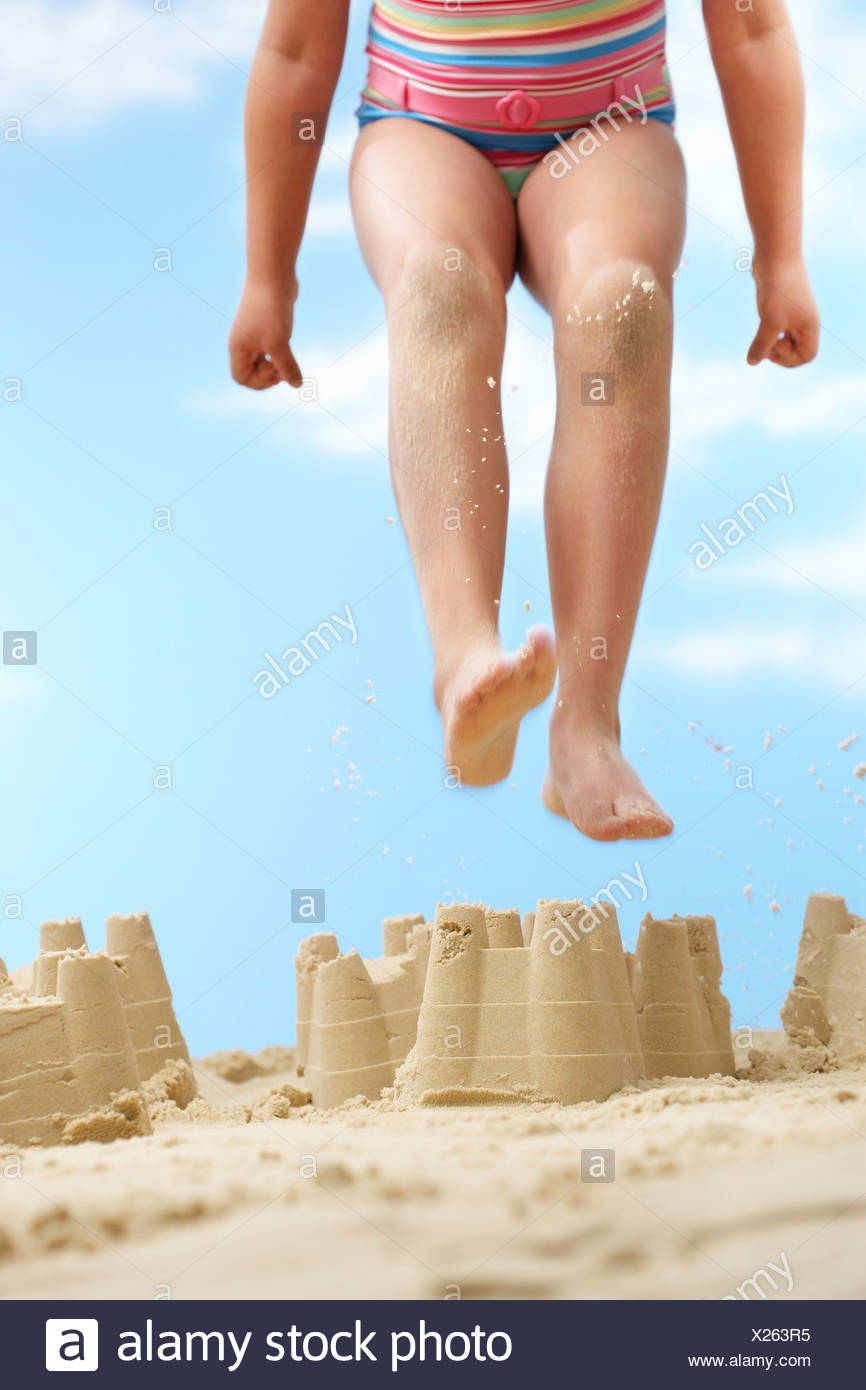 Girl (7-9 years) jumping on sand castle on beach, low section - Stock Image
