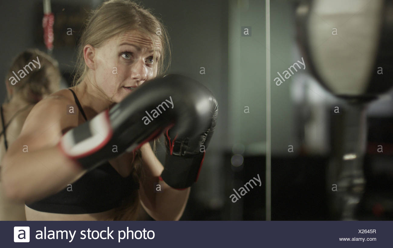 Blurred view of female boxer working out and training with punching ball in gym - Stock Image