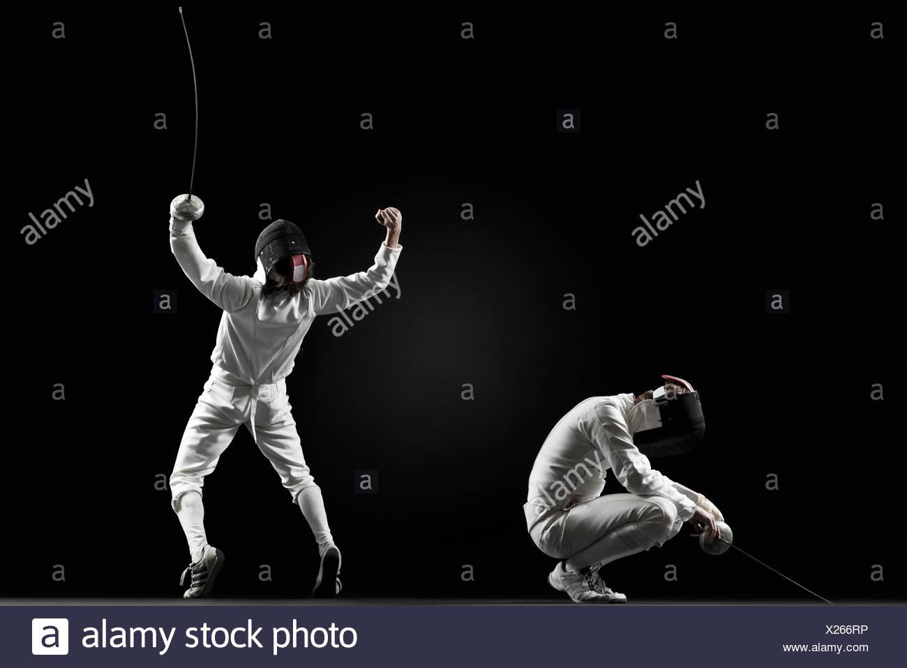 Winning fencer celebrating over defeated fencer - Stock Image