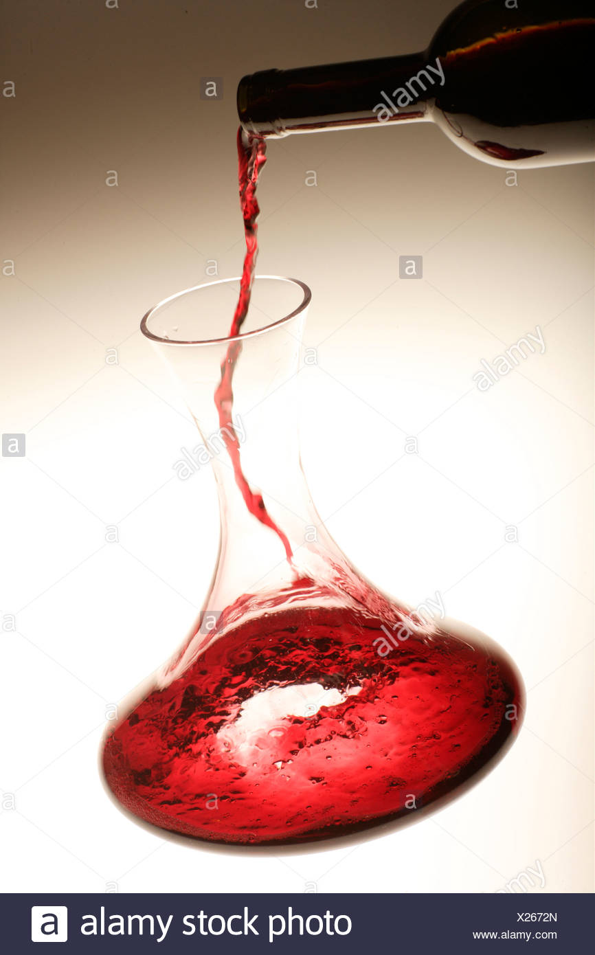 Red wine being poured into a decanter Stock Photo