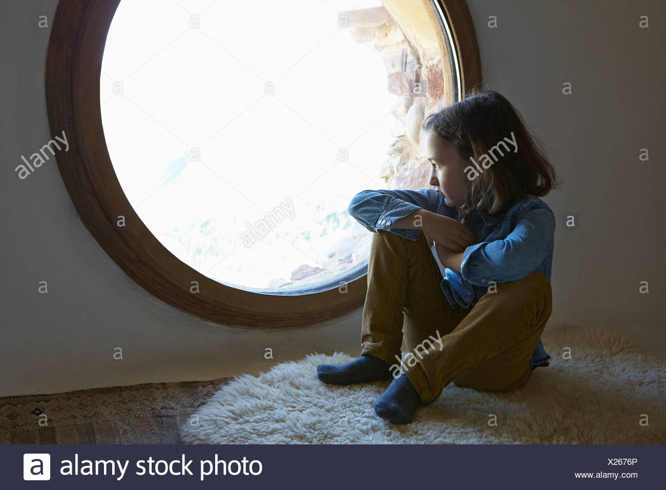 Girl sitting on floor gazing through circular window - Stock Image
