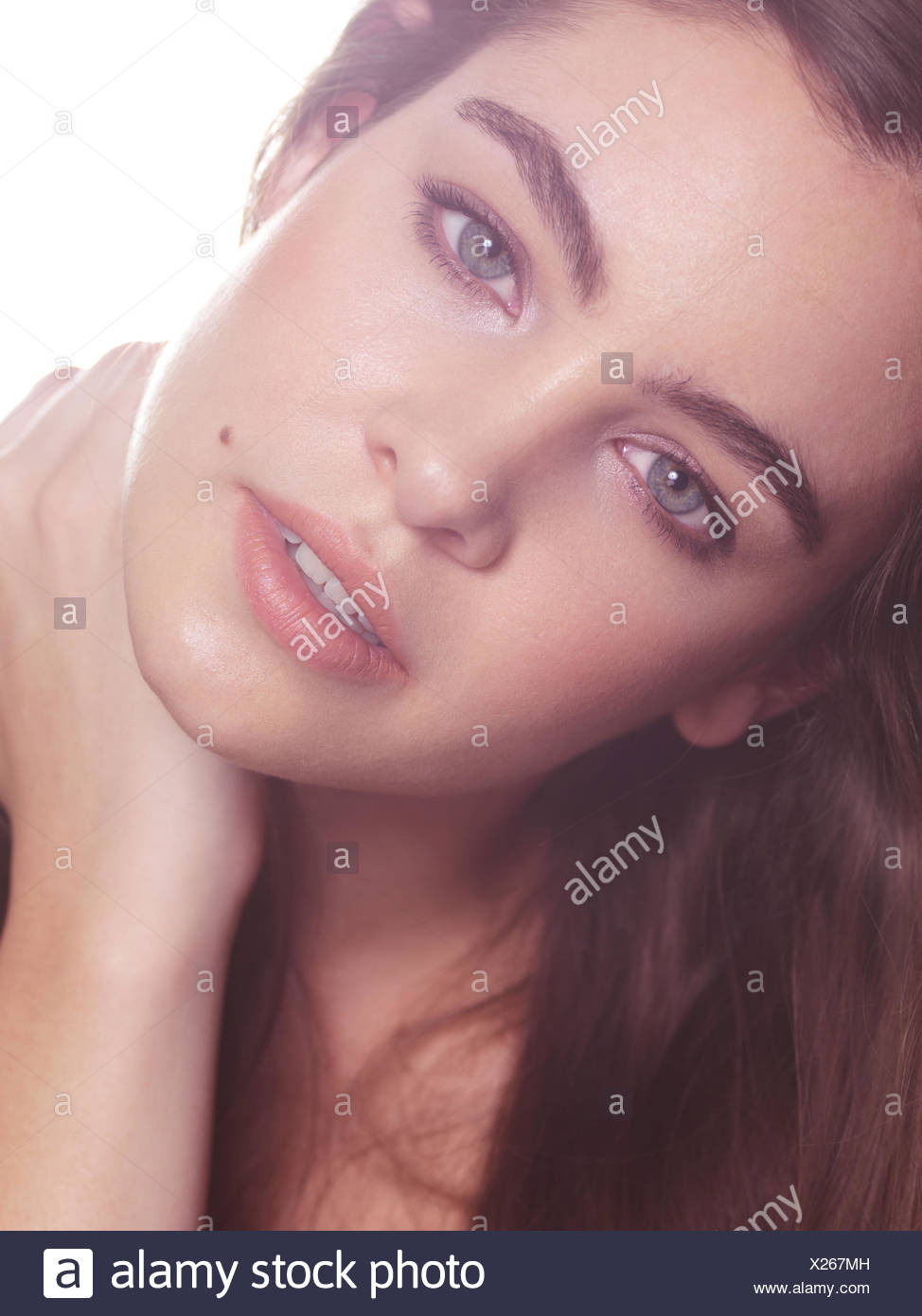 Woman with long hair and bushy eyebrows in soft light - Stock Image