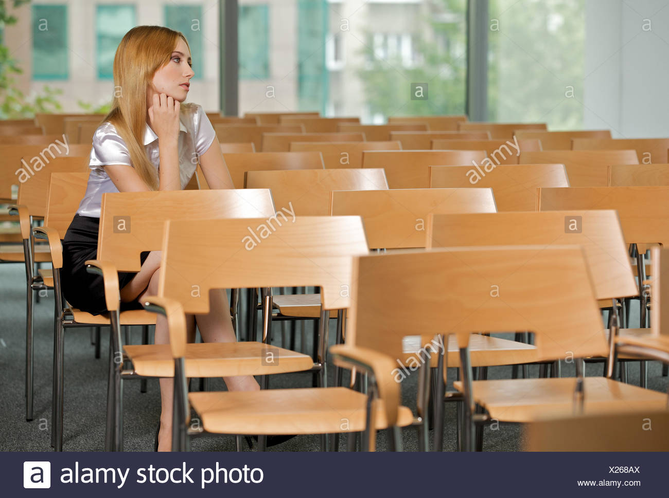 Businesswoman contemplating at conference room in office - Stock Image