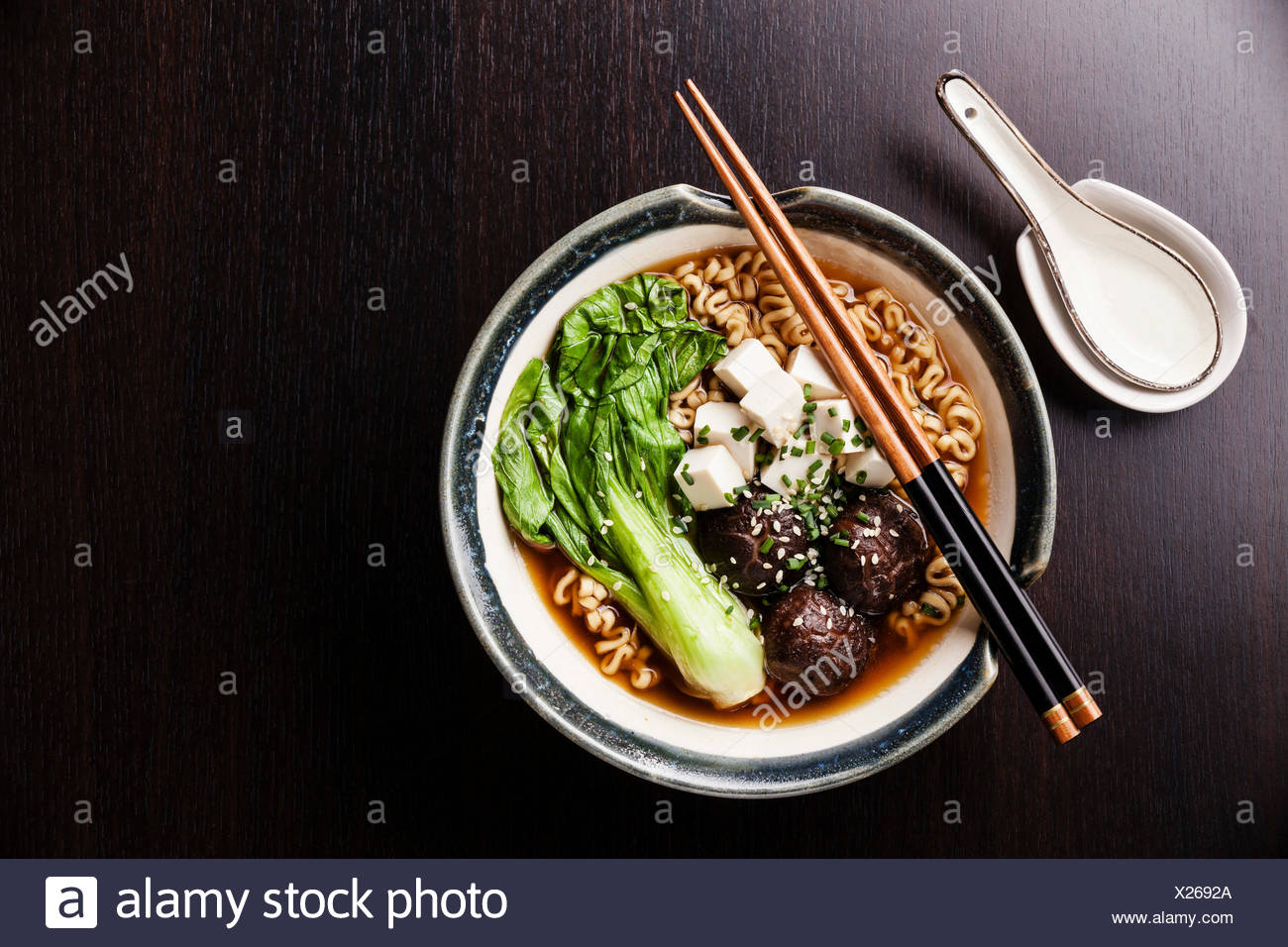 Miso Ramen Asian noodles with shiitake, tofu and pak choi cabbage in bowl on black table background - Stock Image