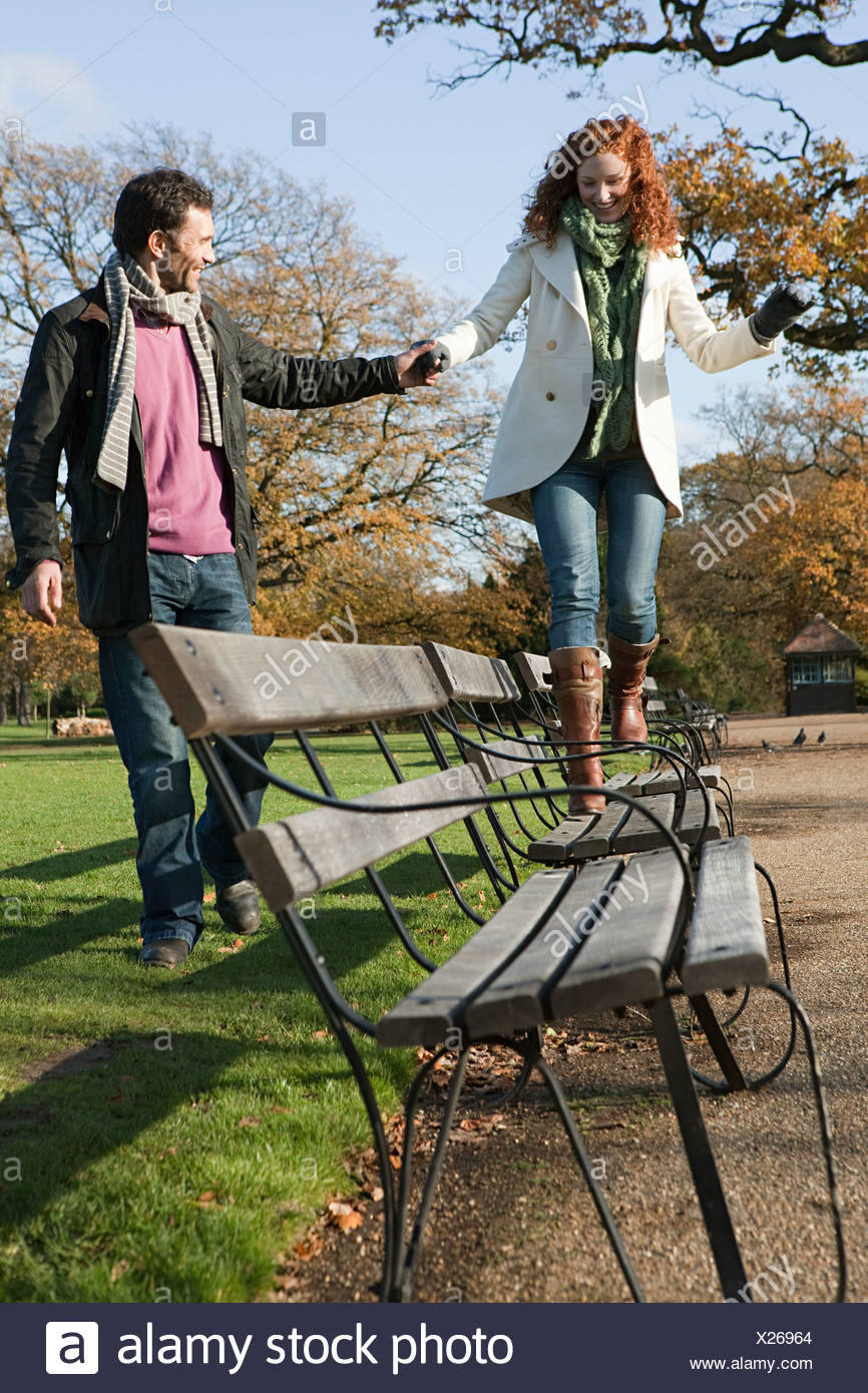 A woman walking across a park bench Stock Photo